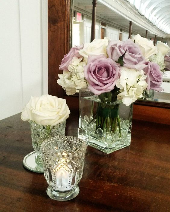 Beautiful wedding decorations by pink pumpkin events! Lavender roses in a vintage glass vase against our antique wooden cabinet at the S.S. Sicamous in Penticton, B.C.