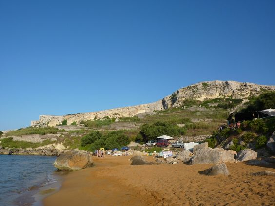 Orange! San Blas Bay auf Gozo hat rotgefärbte Felsen, begrünte Hügel, hellblaues Meer. Der orangefarbene Strand dazu machen San Blas Bay im Nord-Osten von Gozo zu einem bunten Naturspektakel. Trotzdem finden Strandgänger hier wunderbare Ruhe – denn nahe des Ortes Nadur muss das Auto abgestellt werden, da das letzte Stück nur zu Fuß zurückgelegt werden kann.  Reisetipp bei lastminute.de: 4-Sterne Grand Hotel Gozo. © MTA Doritt Schmidt