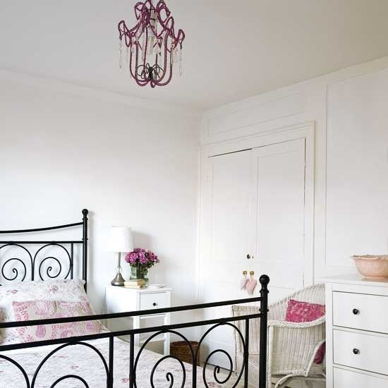 Black metal Ikea bedframe in white bedroom with pink accents