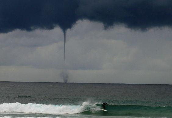 A tornado rises from the sea behind a surfer on Bondi beach in Sydney, Australia