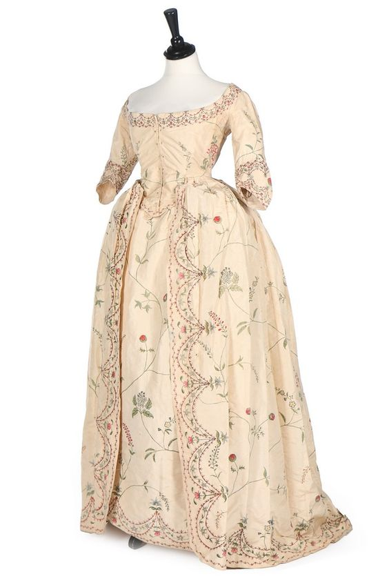 Robe à la polonaise, England, 1770s. Ivory silk taffeta painted to shape in imitation of Chinese silk, the edges and front openings painted with foliate swags with delicate meandering buds and wild flowers over the ground, with cord polonaise ties and loops within the overskirt the petticoat painted to match, lined in wool.