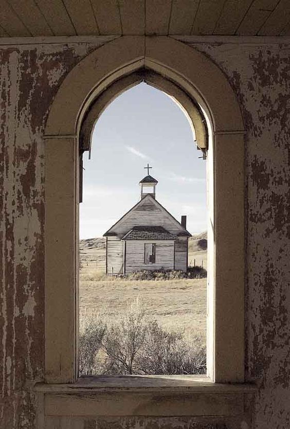 View through the vestibule window of an abandoned United Church in Dorothy, Alberta looking onto an old Catholic Church at the end of a grassed-over dirt road.