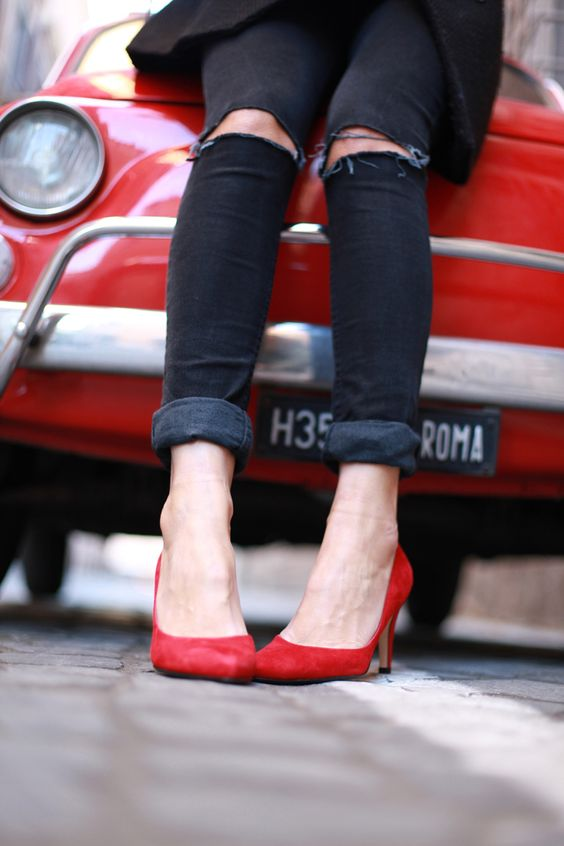 {Distressed denim and red heels.}