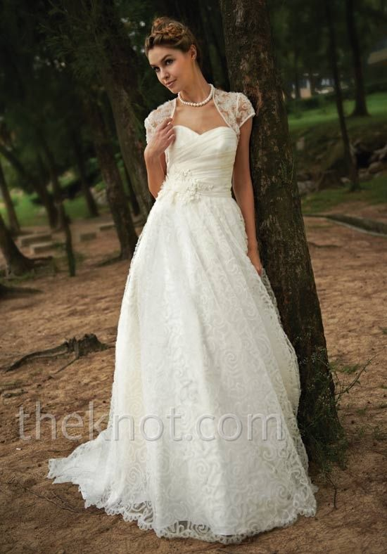Gown features embroidery and lace. Matching jacket, shrug, and veil available.