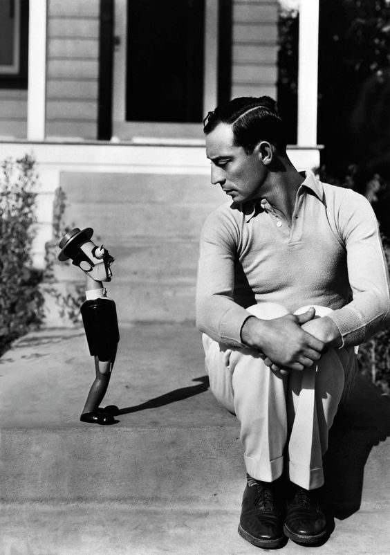 American comic actor Buster Keaton poses with a doll made in his image, United States, 1933, photographer unknown.