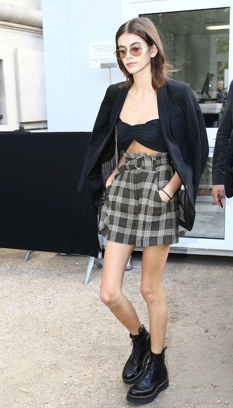 Kaia Gerber wearing a black blazer, black bandeau crop top, plaid skirt with o-ring belt, black combat boots, and brown metal sunglasses