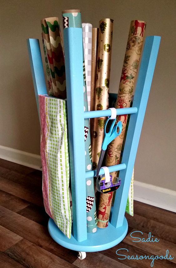 An upturned bar / kitchen stool from the thrift store gets a pretty makeover and an entirely new purpose in life- gift wrap storage!! This easy DIY is so perfect, so functional, so GENIUS, that you'll never want to store your wrapping paper any different way from now on! #SadieSeasongoods