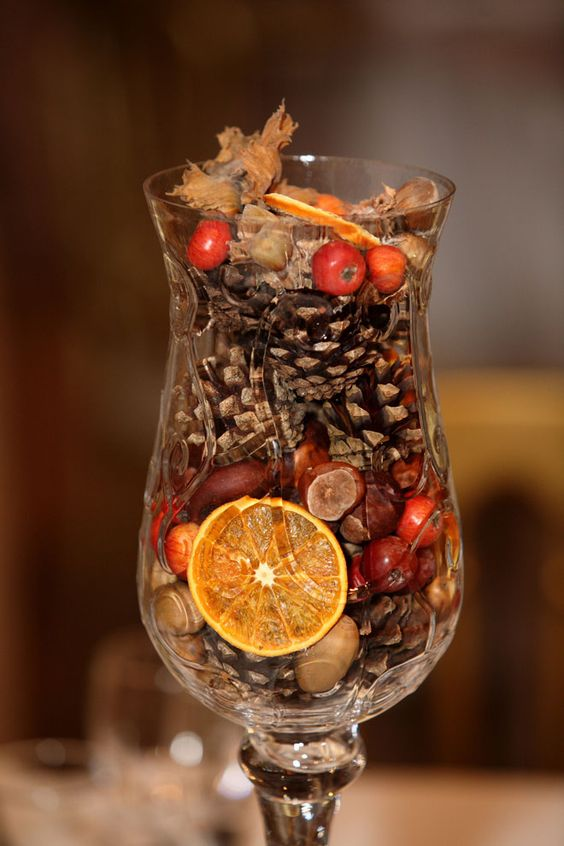 Autumn centre pieces: festive array of seasonal autumnal offerings like pinecones, hazel nuts and colourful segments of dried oranges and rosehips: