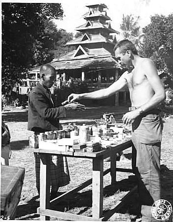 Buddhist Monastery serves as a backdrop for an American aid station where WWII soldier dispenses medical supplies to local Burmese. Photographer Unknown