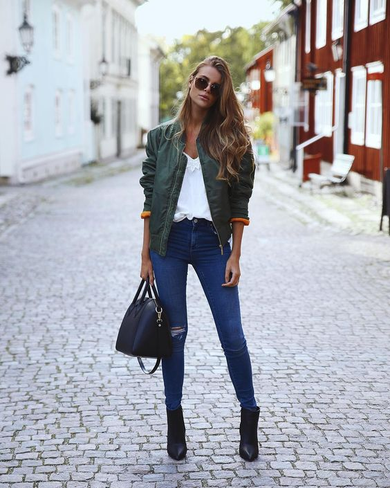 Green bomber jacket + white t-shirt + ripped jeans + black ankle boots + black bowling bag = badass street style this fall and winter.: