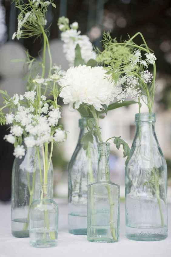 Antique glass bottles and simple white flowers are a lovely combination.:
