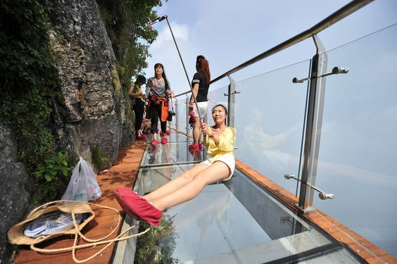 ZHANGJIAJIE, CHINA - AUGUST 01:  A tourist takes a selfie on the 100-meter-long and 1.6-meter-wide glass skywalk clung the cliff of Tianmen Mountain (or Tianmenshan Mountain) in Zhangjiajie National Forest Park on August 1, 2016 in Zhangjiajie, Hunan Province of China. The Coiling Dragon Cliff skywalk, featuring a total of 99 road turns, layers after another, is the third glass skywalk on the Tianmen Mountain (or Tianmenshan Mountain).  (Photo by VCG/VCG via Getty Images) via @AOL_Lifestyle…