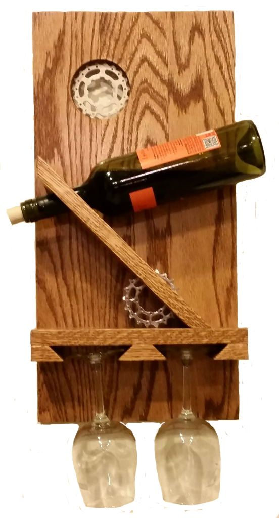 Winecycle Built for Two  This contemporary wooden wine rack holds service for two (a single wine bottle and two wine glasses). Great décor for small spaces. Perfect gift for bicycle enthusiasts, Valentine Day, or Anniversary. Great conversation piece!     Poplar with Natural Cherry Finish with Polyurethane protective coat. Gears may vary depending on materials in stock.