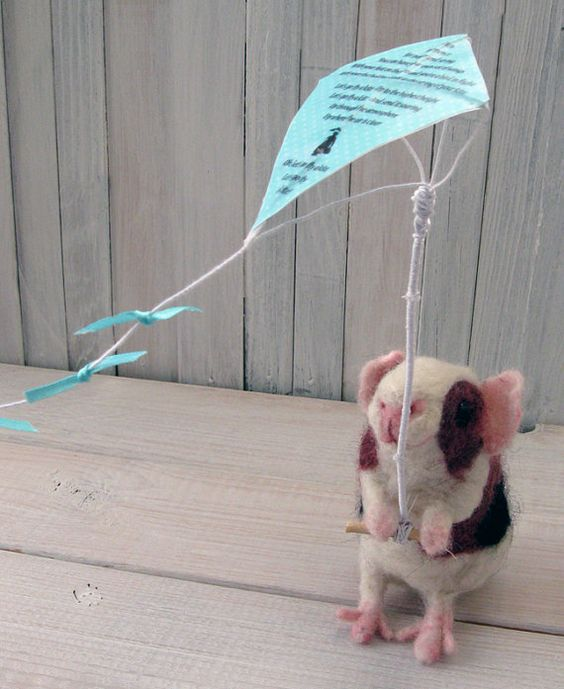 On Etsy. LET'S GO FLY A KITE...    Handmade animal art doll. Needle felted from wool. Pose-able.    This little guinea pig loves spring, and is doing a great job at keeping her kite in the air. If you listen very closely, you can almost hear her humming tunes from Mary Poppins.    The underside of her kite features a picture of the Banks family from the happy end of the movie, out flying their own kites. The top side of the kite has the lyrics to the song.