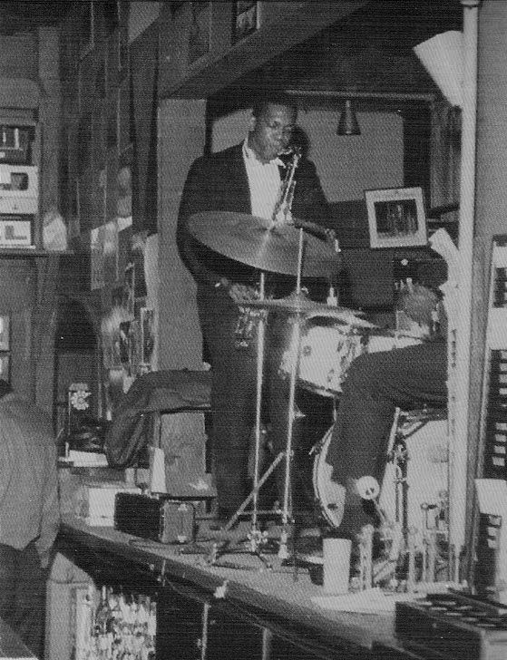 """""""NYC in March 1965.  The photo below is from that Coltrane Quartet concert at the Half Note, which was on the corner of Spring and Hudson Streets in Manhattan.  That stage is tiny and appears to be over the bar. """""""