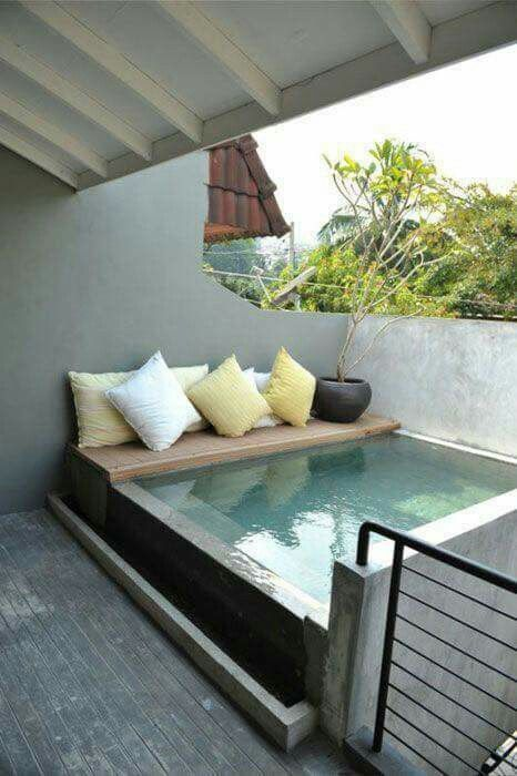 The ultimate balcony plunge pool | Concrete design with cream and yellow throw cushions