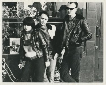 "Teenage Jesus and The Jerks [NY]:: nd.. 8 x 10"" b/w photograph by an unknown photographer. The photo shows the band posed in front of the window of a record store. In the background can clearly be seen the cover of the Ramones 1977 LP Rocket to Russia, and the band appears to be, consciously or unconsciously, mirroring the posture of the Ramones on the record sleeve. A great photograph which we haven't encountered before."