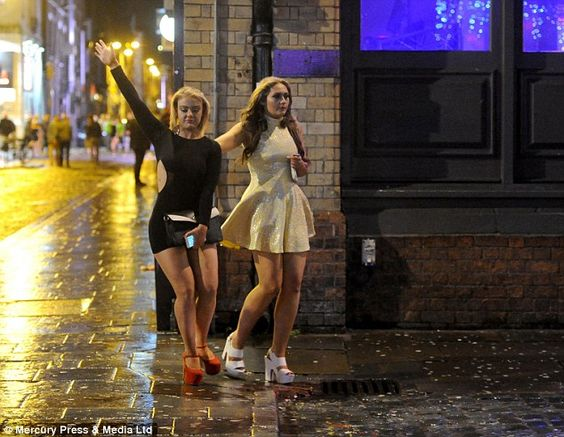 Two young women, wearing short dresses and platform shoes, enjoy a night out in Liverpool ...