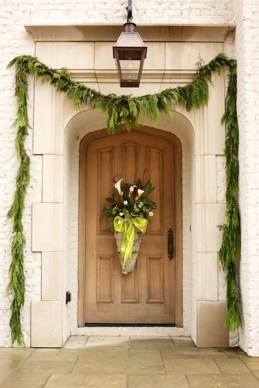 Beautiful natural paneled wood front door adorned simply and elegantly with holiday decor. #frontdoor #holidaydecor #christmasgarland