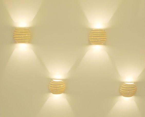 A luz de ressalta as formas orgânicas da Arandela 86, criadas pelos designers Aleverson Ecker e Luiz Pellanda, do escritório Holaria. As peças de porcelana são iluminadas por lâmpadas halopim. Da Lumicenter.