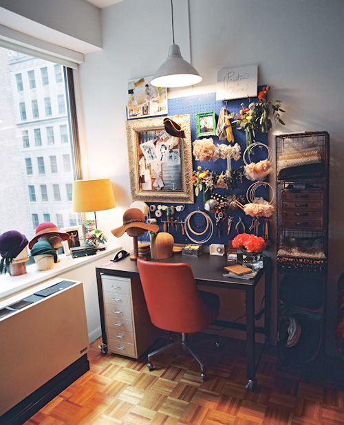 Dara's workspace is all about organization, structure and function. Her desk and wire shelf are from CB2; pendant light and cabinet are from Ikea. When stripped down, the space has a masculine feel (metal desk, with tools and pegboard wall), but feminine touches of beauty are added with Preston & Olivia pieces, fresh flowers and vintage frames.