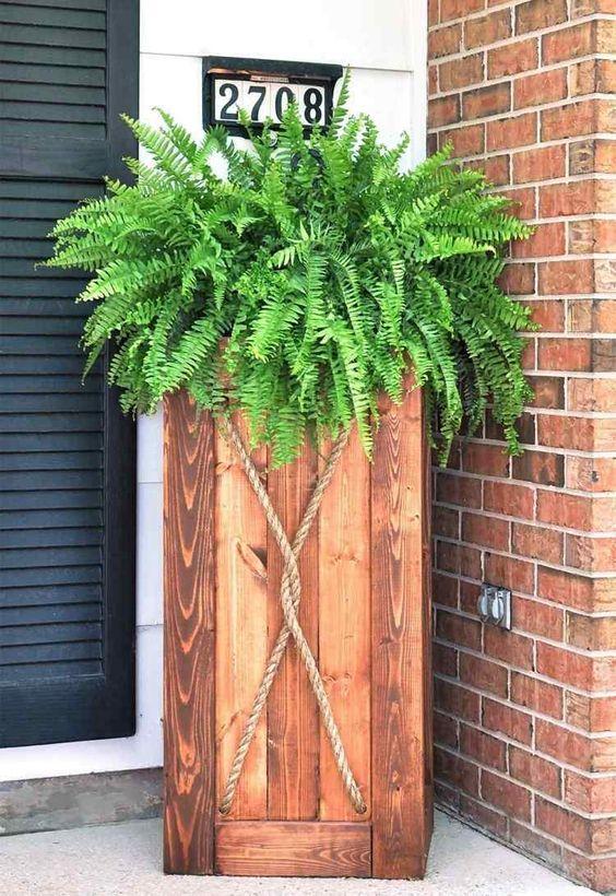 bac à fleurs en bois de design cylindrique avec des fougères