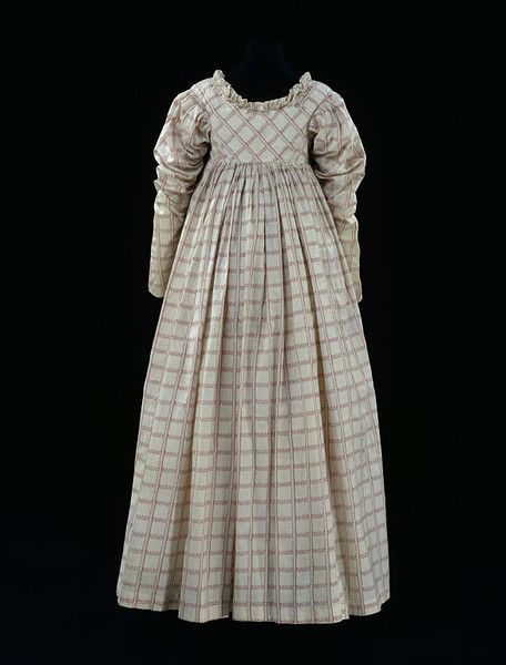 "Ca. 1814  V: ""Thorny stems and leafy bands intersect on this dress, producing a trellis-like effect. They give the cotton a light and delicate appearance, which is heightened by the double neck frill and gathered sleeves."
