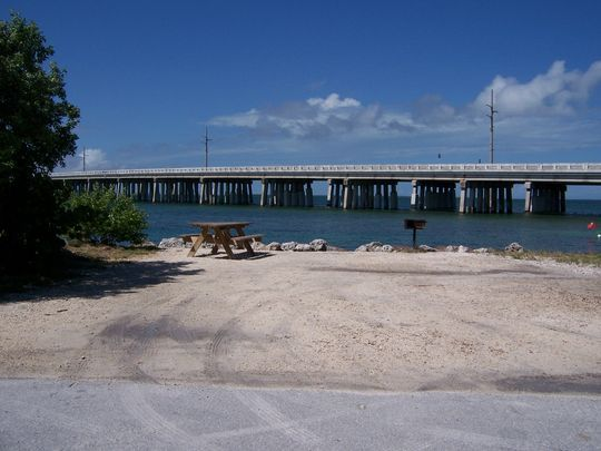 #19 Photo: Buttonwood: Gravel site with picnic table and grill, bushes on left side, water and new Bahia Honda Bridge in the background.