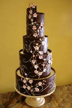 Tall creative four tier brown and pink cherry blossom wedding cake decorated with pink cherry blossoms.