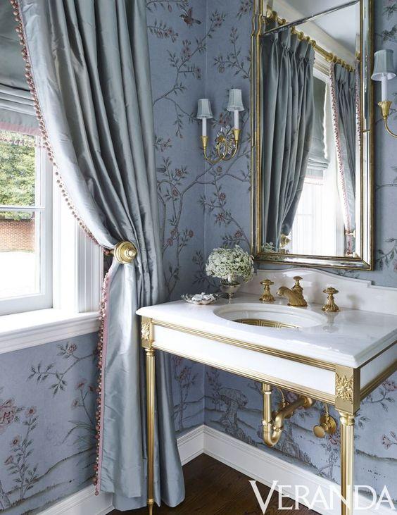 Classic bathroom design with traditional decor including blue wallpaper, formal drapery, and console sink. #bathroomdesign #bluebathroom #interiordesign #traditionaldecor