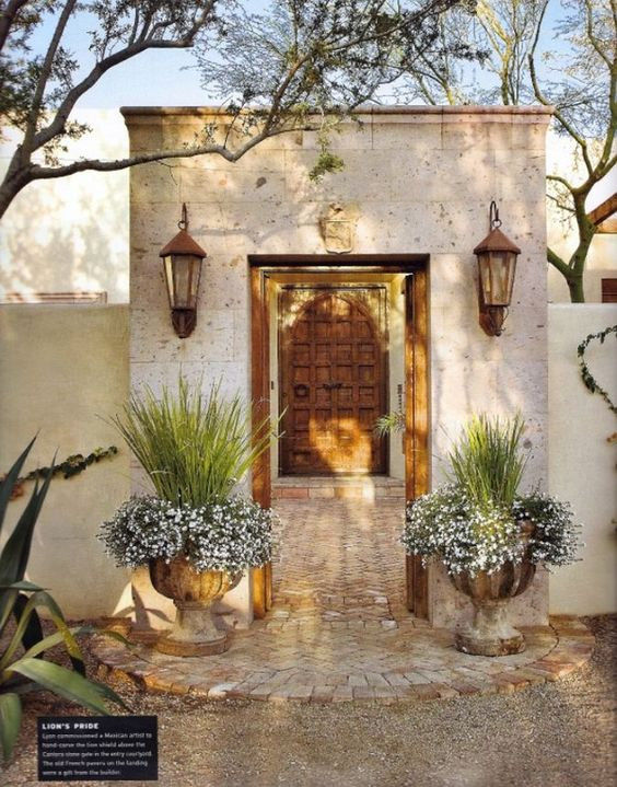 French urns flank entry to spanish style courtyard palm for French style courtyard ideas
