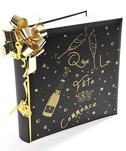 Le livre d'Or Que la Fête Commence Luxueux livre d'or à la couverture satinée avec un message incrusté de petites paillettes scintillantes : Que la Fête Commence avec une bouteille de champagne et deux coupes.