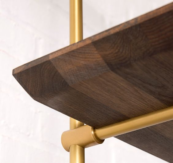 The Collector's Shelving System is fully adjustable and designed to be configured for any space. Shelves and credenza in oxidized oak, framework in solid brass with a warm finish.