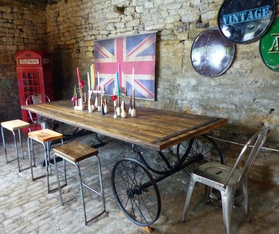 Reclaimed Wooden, Retro industrial Dining Table  on wheels. A large piece of recycled wood furniture. This rustic, industrial dining table rolling on mail cart wheels was made for season 2 of Money for Nothing on BBC2. Handmade with repurposed royal mail cart wheels and reclaimed pine barn doors. Made by forge creative. This designer table is Due to Air this April 11th 2016. 345 pm Now for sale at smithers of stamford