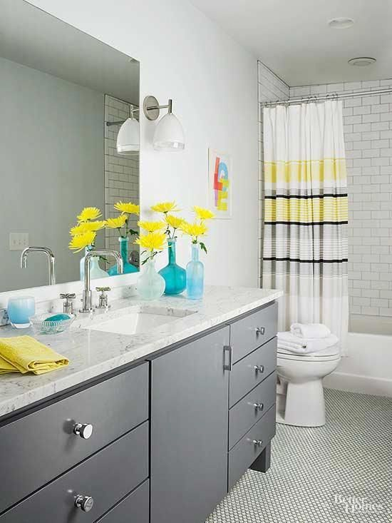 An All White Bathroom Gets An Energy Boost With Accents Of Yellow And Gray Yellow Accents Sit Ato Bathroom Color Schemes Yellow Grey Bathroom Yellow Bathrooms