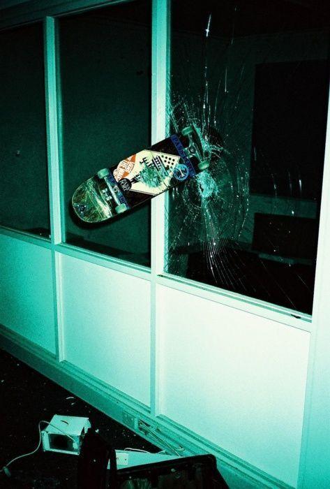 窓ガラスに突き刺さるスケートボード