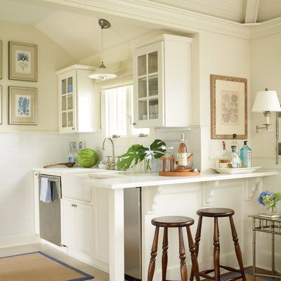 The open and airy kitchen has a farmhouse sink, glass-fronted cabinetry, and a breakfast bar that's perfect for a small gathering.: