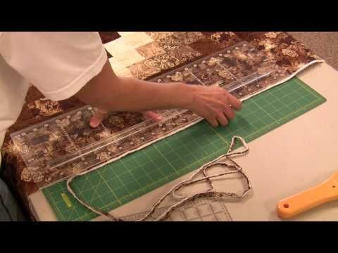 "As you get ready for binding, it's important that the quilt is straight. Our fourth video shows how to cut around your quilt making it ready for binding.     A special thank you to Karen Reardon for letting us use her quilt, ""Sunshine and Shadows"" for the demonstration."
