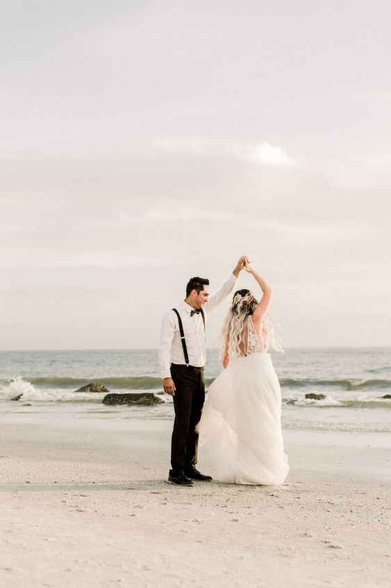 Bride and groom twirl in celebration during their celestial themed beach wedding photography shoot. The bride is wearing a long, flowy dress, hair with dark brown to white blonde ombre, while the groom is wearing a modern take on the classic suit - suspenders only, sans jacket. | Celestial Wedding Inspiration with Incredible Star and Moon Details | #equalitymindedweddings #lgbtweddingmagazine #loveinc #beachwedding #bohowedding #floridaweddings
