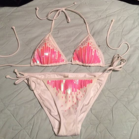 White bikini with pink sequins Light padding in the top. The padding on the top  slightly yellowed about (only on the inside where no one can see anyway) after I wore it in the ocean? This is not noticeable though, and I've only worn this bikini a couple of times--still in excellent condition! Victoria's Secret Swim Bikinis