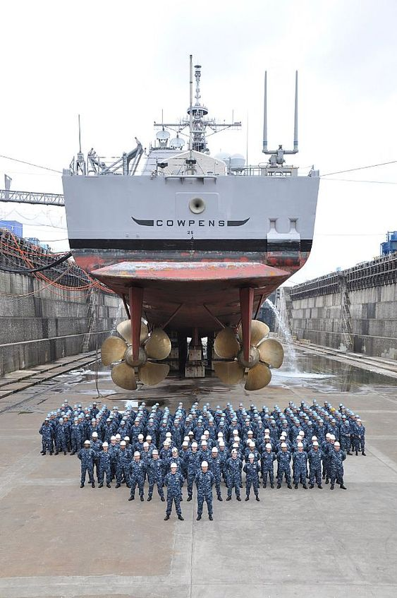 YOKOSUKA, Japan (July 6, 2010) The officers and crew of the guided-missile cruiser USS Cowpens (CG 63) pose for a group photo under the ship at Fleet Activities Yokosukas dry dock six.: