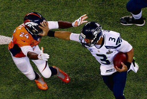 Russell Wilson giving the ol' stiff arm to Champ Bailey