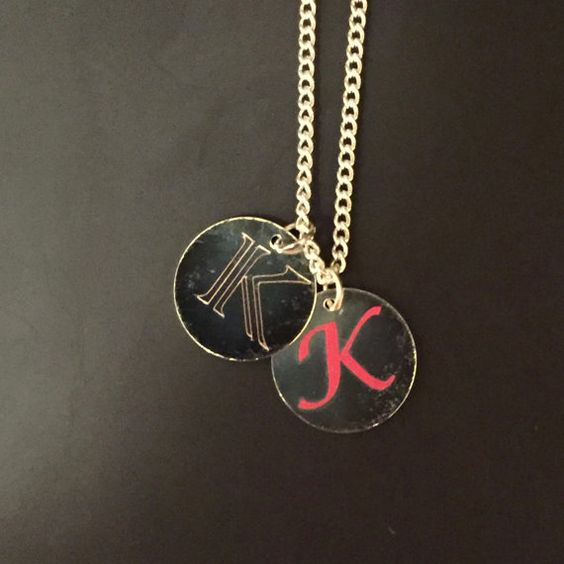 This necklace can be customized with any initial. The two charms can be worn together or separately. One charm is etched onto a 3/4 inch diameter silver plated brass disc and the other is stamped onto a 3/4 inch diameter silver plated brass disc with pink permanent vinyl.