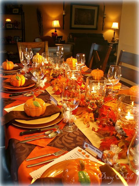 Dining Delight: Fall Dinner Party for Ten. Orange brown yellow. 5 double wall hurricane vase centerpiece. Outside filled with river rocks, inside with orange gems, water, floating candles. Place setting: gold charger, orange plate, pumpkin tureen. Looks like placemat is orange napkin turned in diamond shape.