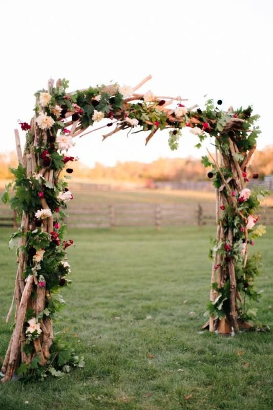 Rustic Wedding Decor Idea A Wood Ceremony Arch Consisting Of Branches Greenery And Jewel Toned Flowers