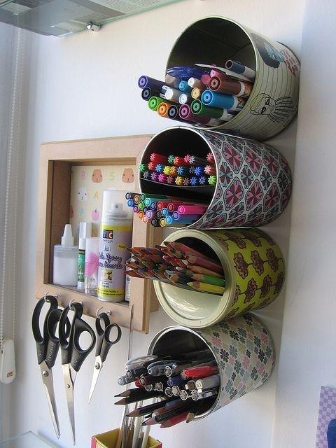 Latas encapadas e fixadas à parede mantêm canetas, lápis e acessórios separados e à mão.: