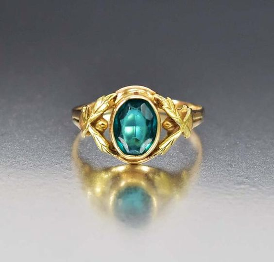 Evocative of the Victorian era, this distinctive and lovely 1930s Art Deco ring makes a wonderful alternative engagement ring. A simulated emerald stone is face