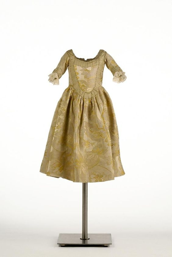 Girl's dress, Spain, c. 1780. Golden yellow and silver silk brocaded with floral motifs.
