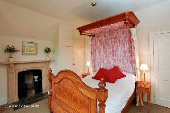 Large double Canopy bed inside Evesham House with original working stone fireplace, hanging storage and shower room adjacent but not en-suite                    #Cotswolds #holiday #rental