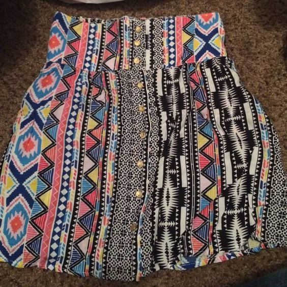 Fun Aztec skirt!! Bright bold colors, Aztec designs with gold buttons down the middle of the front side. Super cute on!!  Charlotte Russe Skirts